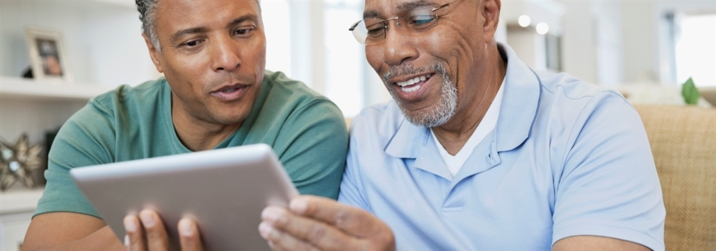 two men looking at digital device